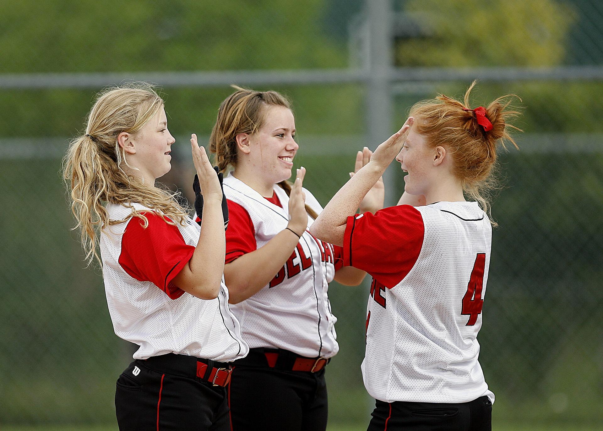 girls softball team giving each other high fives