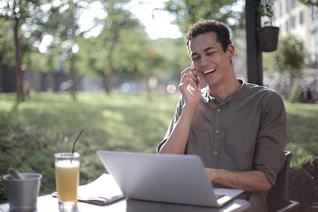 man on phone using his lap top image