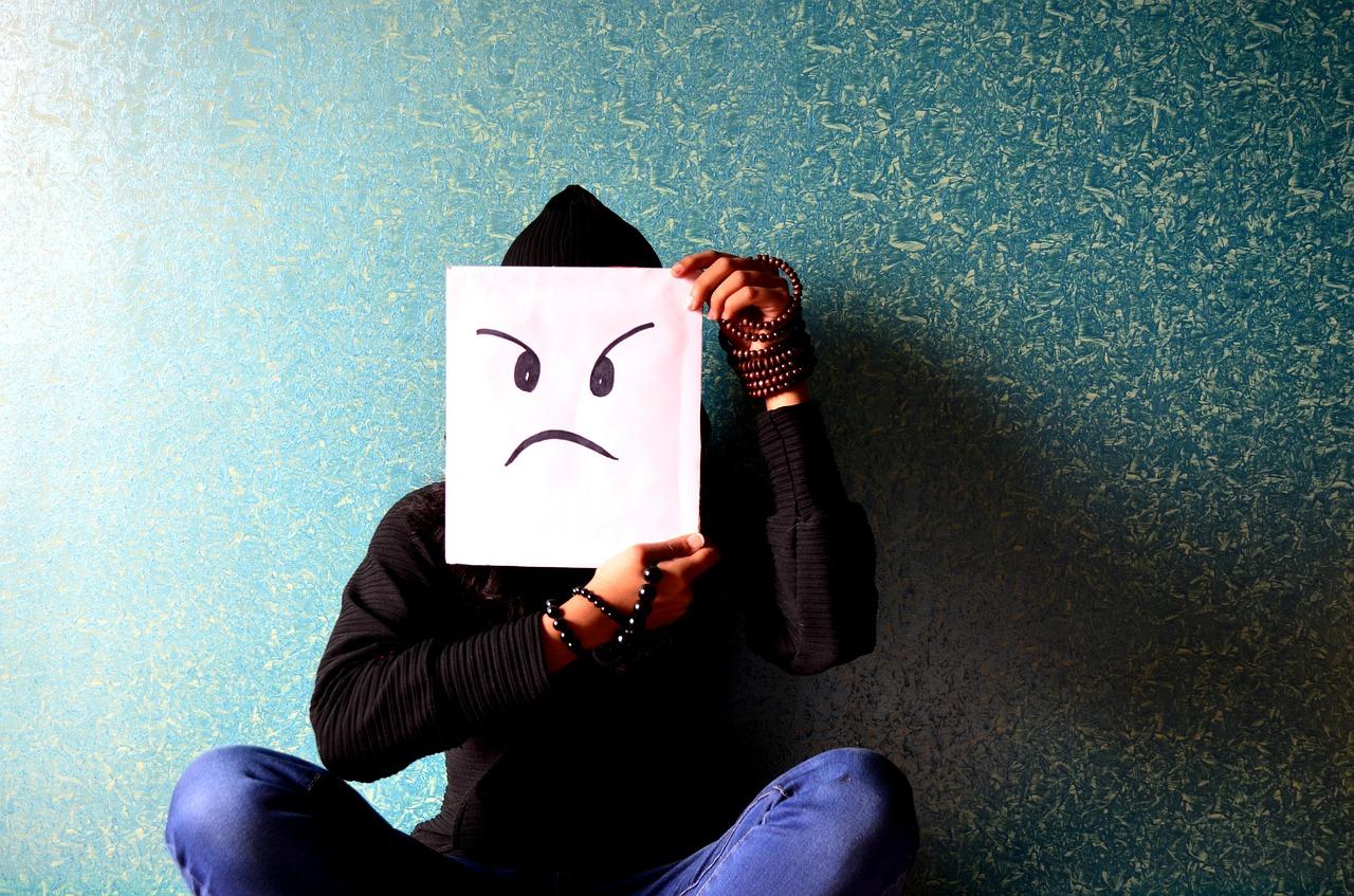 photo of someone holding drawn sad face