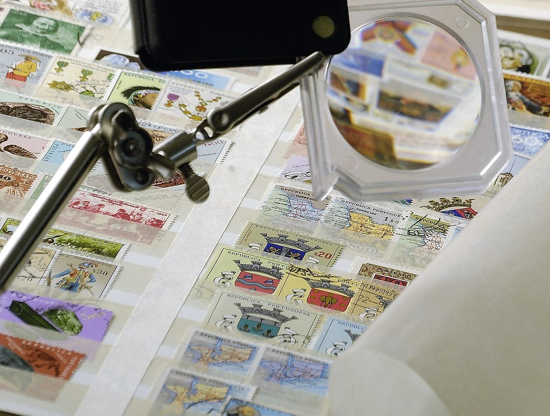 looking at stamps under a magnifying glass